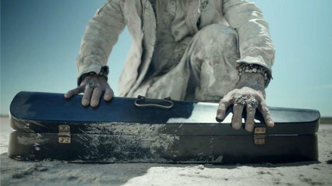 Fotograma en el que aparece la funda de un violín en el suelo y unas manos abriéndola