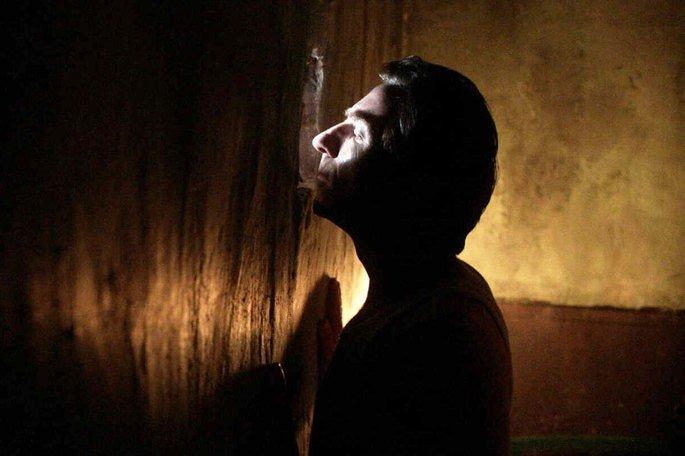 Fotograma de la película en el que Higinio, el protagonista, está escondido y vigila el exterior
