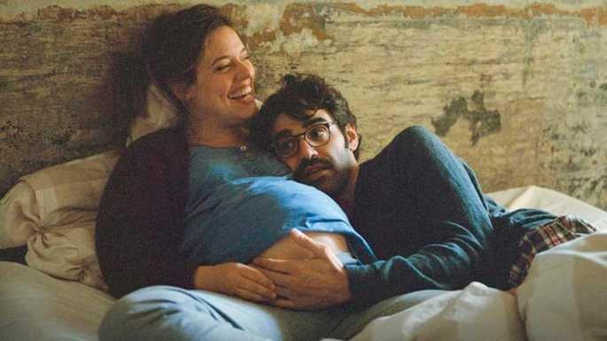 Fotograma de la película en el que los protagonistas están tumbados en la cama sonriendo