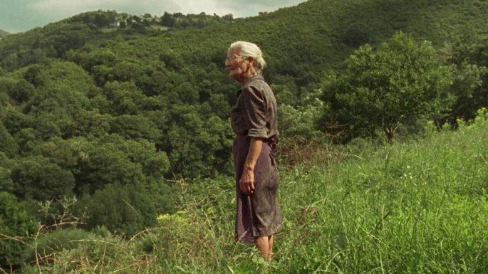 Fotograma de la película O que arde, Benedicta en el centro de la imagen rodeada de vegetación