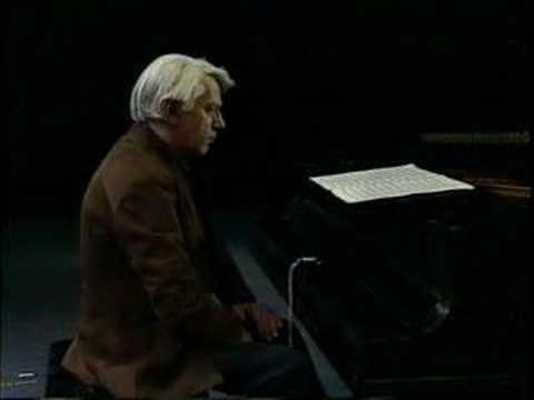 Homem sentado à frente de um piano sem tocar nada