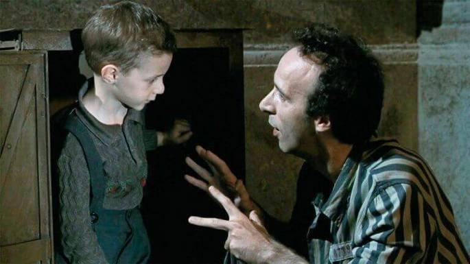 cena de filme A vida é bela mostra pai e filho durante a guerra