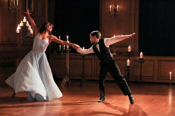 filme Across Grace Alley. Um garoto bem vestido e uma mulher com vestido esvoaçante dançam em salão elegante