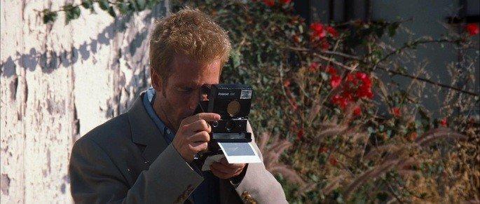 Frame: Leonard tirando fotografias.