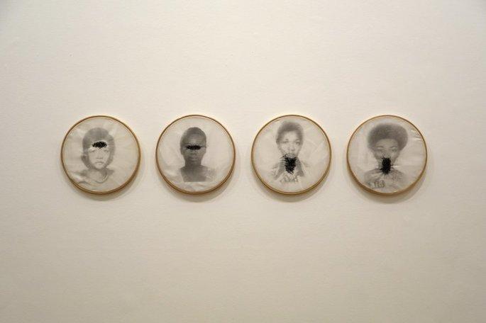 Obra de Rosana Paulino exibindo imagens de mulheres negras com bordados pretos em bocas, olhos e garganta