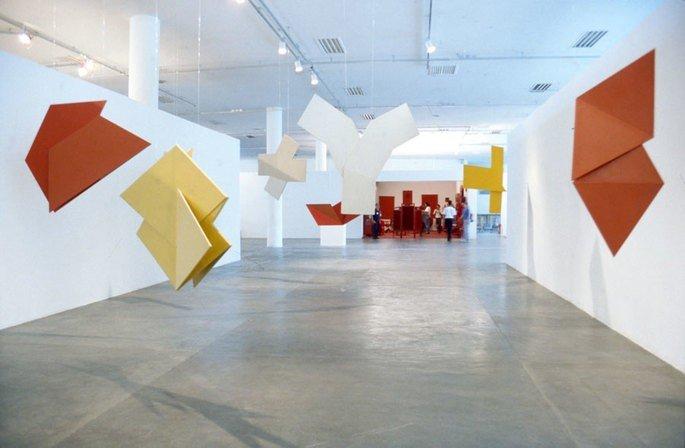 obra de Helio Oiticica mostra placas de madeira suspensas pintadas em cores vibrantes