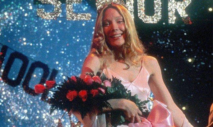 Carrie no baile da escola, recebendo flores e uma faixa de rainha do baie