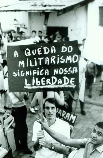 Foto de um protesto de 1968, jovem segura um cartaz pedindo o final do militarismo.