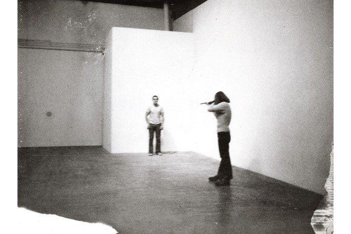 Homem apontando uma arma para outro homem. Performance Shoot, de Chris Burden