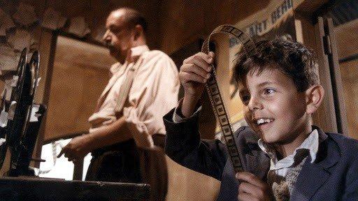 Cena de filme Cinema Paradiso exibe menino olhando negativos de cinema