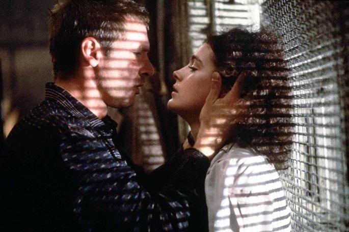 Deckar e Rachel prestes a se beijar em janela que exibe a luz entrando pela grade