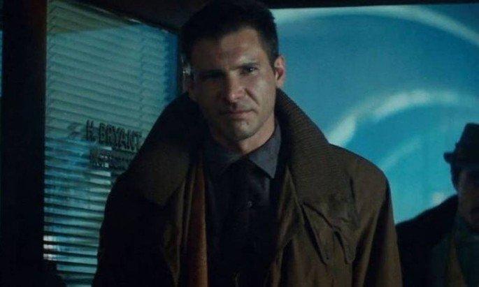 Harisson Ford vive Deckard em blade runner. Ele está de pé com um casaco marrom e atmosfera azulada