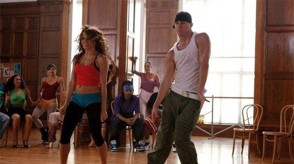 cena do filme Ela dança, eu danço. Um casal jovem com roupas coloridas dança em sala iluminada por grande janela.