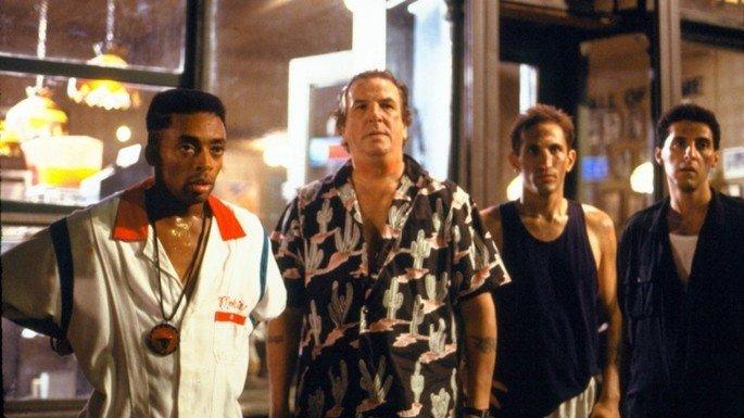 Grupo de homens, com expressão de choque. Um deles está vestindo o uniforme de uma pizzeria.