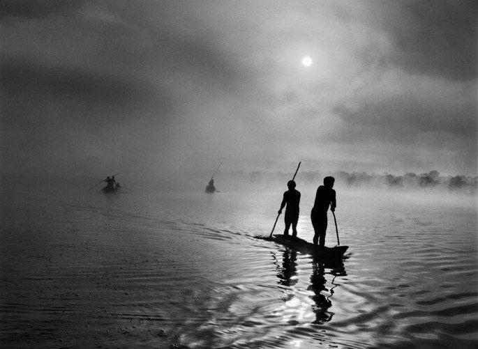imagem de índios em canoas navegando no rio na exposição Gênesis, de Sebastião Salgado