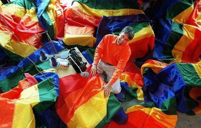 Gilbert Baker rodeado de bandeiras LGBT.