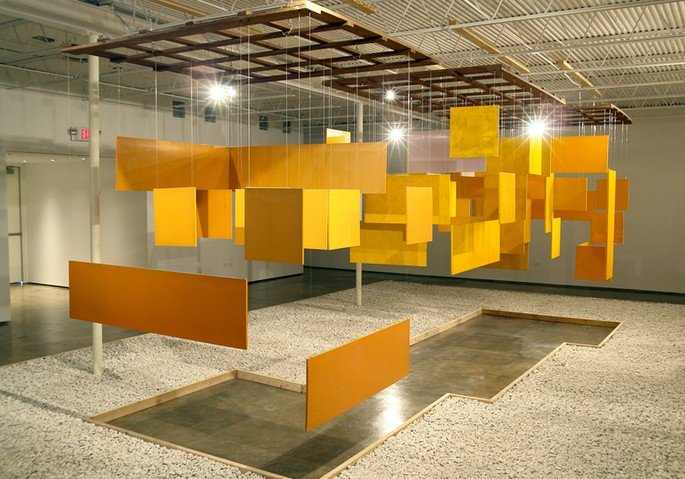 Obra Grande Núcleo, de Helio Oiticica exibe placas de madeira suspensas pintadas de amarelo