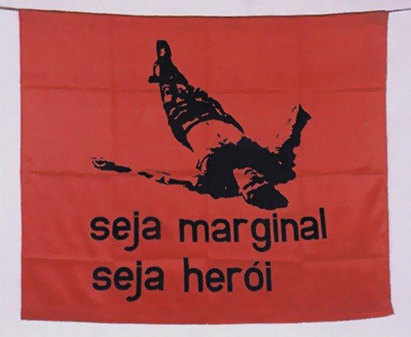 obra de Helio Oiticica mostra tecido vermelho com imagem de pessoa caída e a frase 'seja marginal, seja herói'