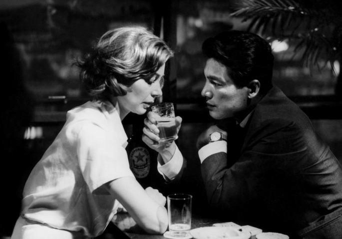 Fotografia em preto e branco de um casal num bar, bebendo cerveja, frente a frente
