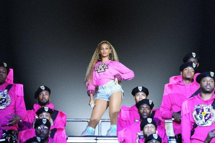 diva pop Beyoncé em cena do filme Homecoming posa com bailarinos em show vestindo roupa rosa