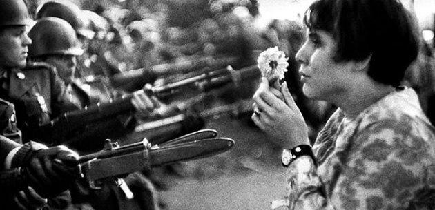 Retrato de mulher nos anos 60 segurando uma flor diante dos militares.