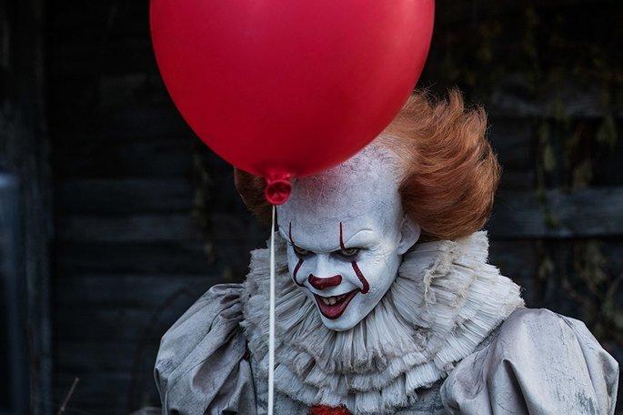 Palhaço rindo, com uma expressão sinistra, segurando um balão vermelho