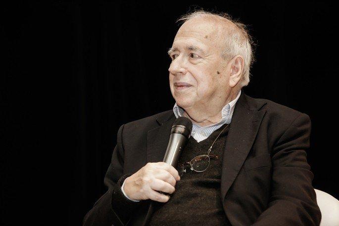 Retrato de Luis Fernando Veríssimo exibe fotografia do escritor em perfil segurando microfone em fundo preto