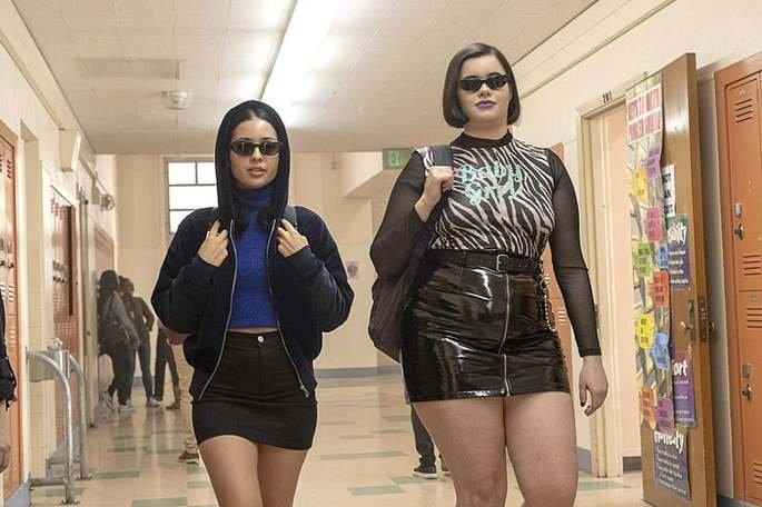 Maddy e Kat, de óculos escuros, no corredor da escola