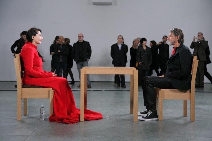 Mulher com vestido vermelho e homem de roupa escura sentados frente a frente