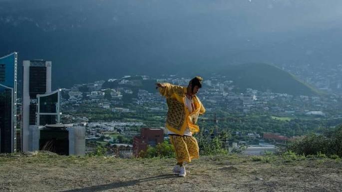 filme mexicano Ha no estou aquí. Jovem mexicano com roupas coloridas dança em lugar ao ar livre com vista da cidade ao fundo