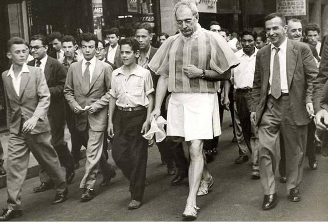 homem caminhando na rua com saia ao redor de transeuntes