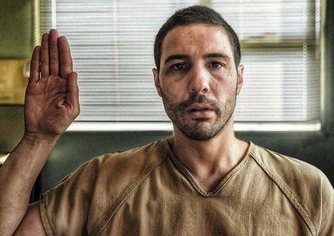 Homem com roupas de prisioneiro, levantando a mão para dar depoimento á justiça