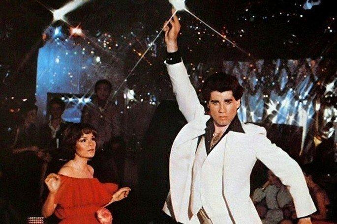 cena de Os embalos de sábado à noite. Casal dança em pista de boate iluminada.