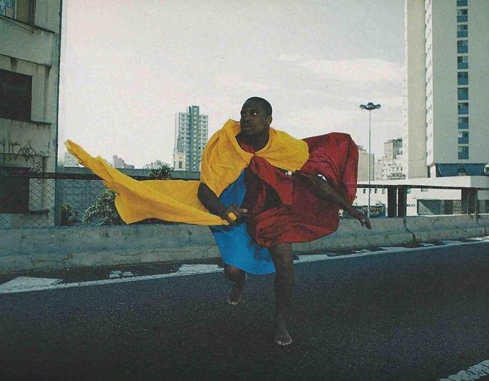 Parangolé, obra de Hélio Oiticica, exibe homem negro dançando com tecidos coloridos