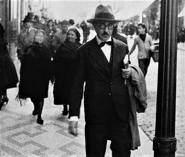 Retrato de Fernando Pessoa caminhando nas ruas de Lisboa.