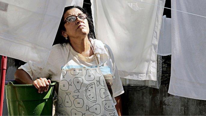 Mulher, de branco, olhando os lençóis secando na corda
