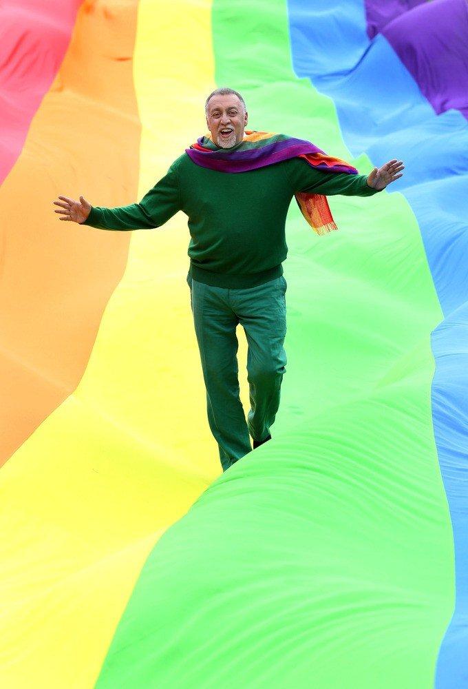 Gilbert Baker caminhando sobre a bandeira arco-íris gigante.