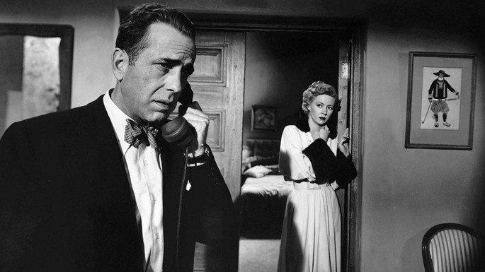 Imagem em preto e branco, com um homem falando no telefone e, no fundo, uma mulher escutando atrás da porta