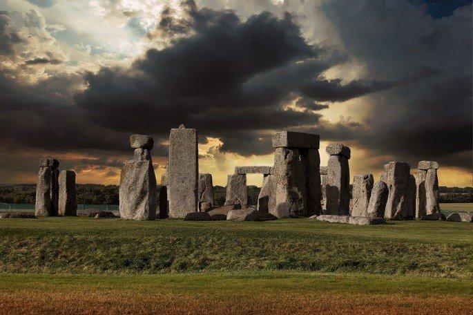 monumento de pedras feito no período neolítico. Pedras dispostas em campo verde com nuvens negras no céu