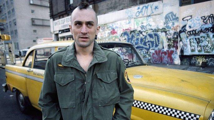 Homem, com cabelo de crista, na frente de um taxi amarelo