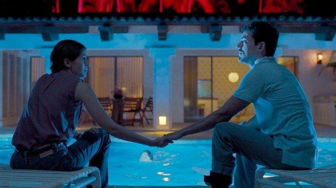 cena de filme Tempo compartilhado exibe um casal a noite à beira da piscina