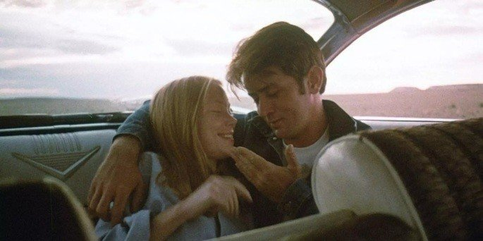 Casal jovem, sentado no banco de trás de um carro, abraçado