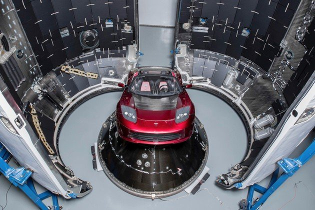 Imagem do interior da Falcon Heavy que carrega um tesla roadster com loop infinito de Space Oddity.