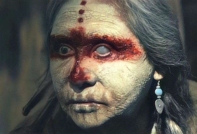 Mulher mais velha, indígena, com o rosto pintado e uma expressão assustadora
