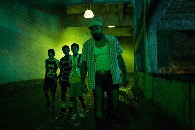 Homem e garotos numa sala verde, como se espiassem alguma coisa