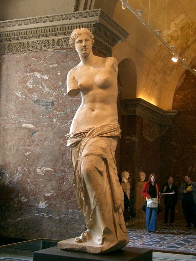 Venus de Milo, no Louvre, sendo admirada pelo publico.